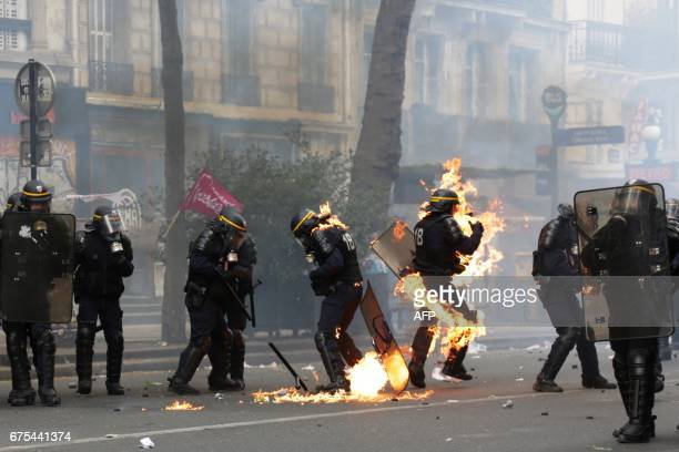 French CRS antiriot police officers are engulfed in flames as they face protesters during a march for the annual May Day workers' rally in Paris on...