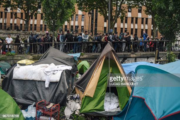 French CRS antiriot police officers stand guard by migrants and refugees queing during the evacuation by police of their makeshift camp along the...