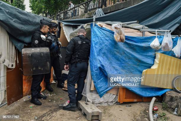 French CRS antiriot policemen check tents during the evacuation by French CRS antiriot policemen of their makeshift camp along the Canal de...