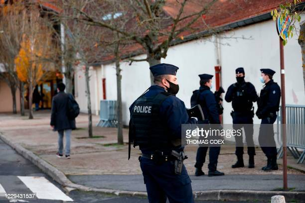French CRS police officers stand near the entrance of Le Bois d'Aulne middle school in Conflans-Sainte-Honorine, 30kms northwest of Paris, on...