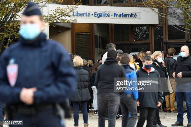 French CRS police stands as adults and children gather in front of flowers displayed at the entrance of a middle school in Conflans-Sainte-Honorine,...