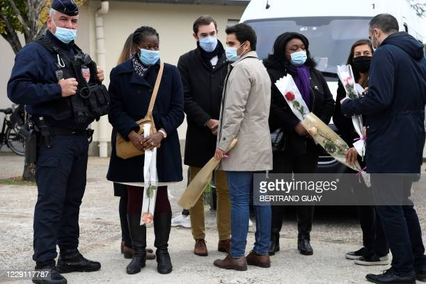 French CRS policeman stands as people hold roses in front of a middle school in Conflans-Sainte-Honorine, 30kms northwest of Paris, on October 17...