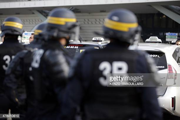 French CRS riot police arrive to intervene as demonstrators block Porte Maillot in Paris on June 25 as hundreds of taxi drivers converged on airports...