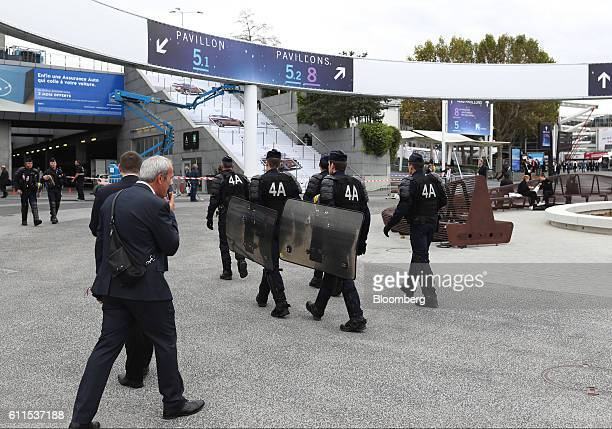 French CRS riot police carry shields as they walk between pavilions at Porte de Versailles exhibition center during the second press day of the Paris...