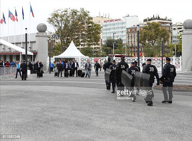 French CRS riot police carry shields as they walk near the entrance of Porte de Versailles exhibition center during the second press day of the Paris...