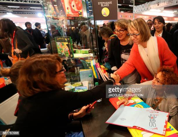 French Culture Minister Francoise Nyssen shakes hands with attendees as she visits the inauguration of the Montreuil Youth Book Fair at Montreuil on...