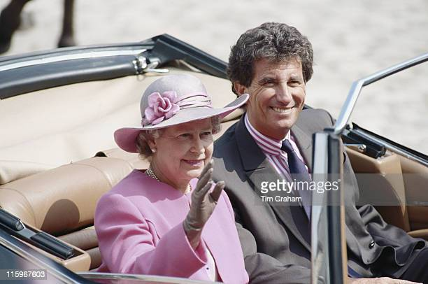 French Culture Minister Jack Lang and Queen Elizabeth II waving as they ride in a carriage during the Queen's visit to the Chateau De Blois in Blois...