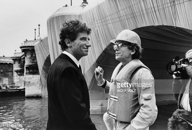 French culture Minister Jack Lang chats with US Bulgarian born artist Christo on September 18 1985 in Paris during the work in progress of the Pont...