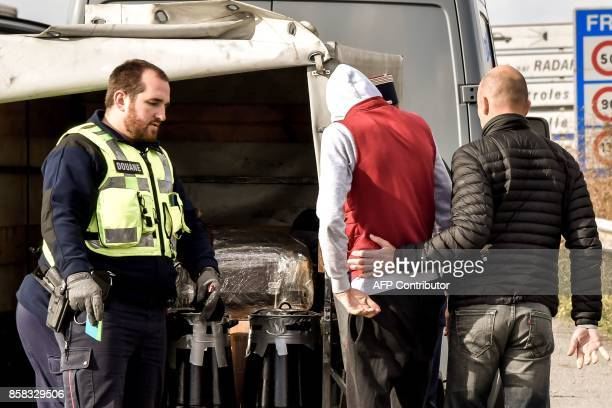 A French custom officer moves aside the driver of the pickup to let his colleagues conduct investigations and searches on the highway A27 during a...