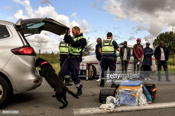 French custom officers conduct investigations and searches with a dog on a car and its conductors on the highway A27 during a French and Belgian...