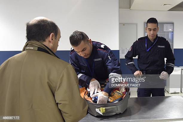 A French customs officer checks luggage on March 17 2015 at Roissy CharlesdeGaulle airport north of Paris AFP PHOTO / DOMINIQUE FAGET