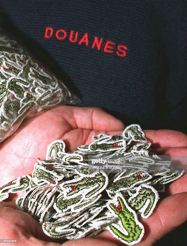 eaf4f4aee644 A French customs officer displays a handful of fake Lacoste ...