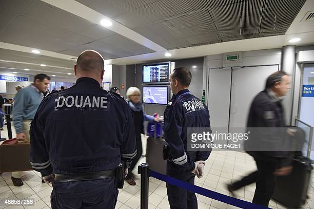French customs officer watch passengers on March 17 2015 at Roissy CharlesdeGaulle airport north of Paris AFP PHOTO / DOMINIQUE FAGET