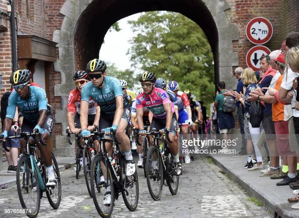 French cyclist Bryan Coquard wearing the overall leader's pink jersey rides in the pack on cobblestones during the fifth stage of the Four days of...