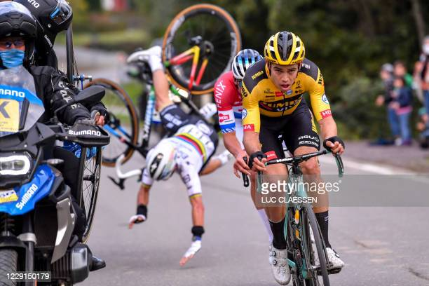 French cyclist Julian Alaphilippe of Deceuninck - Quick-Step falls after crashing into a motorbike, as he rides behind Belgian Wout Van Aert of Team...