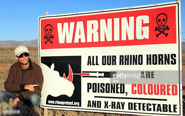French Damien Vergnaud poses next to a sign warning poachers that rhino horns have been poisoned on March 22 2013 at his private game reserve in...