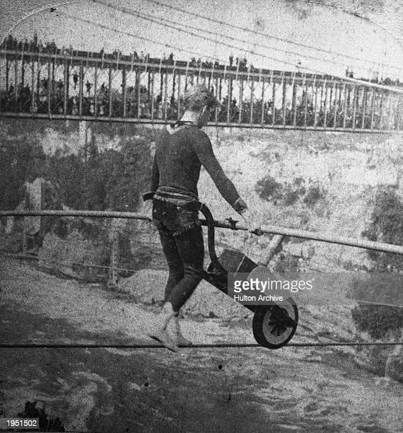 French daredevil Jean Francois Gravelet Blondin aka 'The Great Blondin' pushes a wheelbarrow while tightrope walking across the Niagara River Gorge c...
