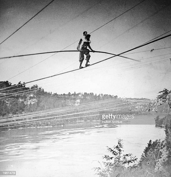 French daredevil Jean Francois Gravelot, a.k.a 'The Great Blondin,' tightrope walks across the Niagara River Gorge carrying his manager, Harry...