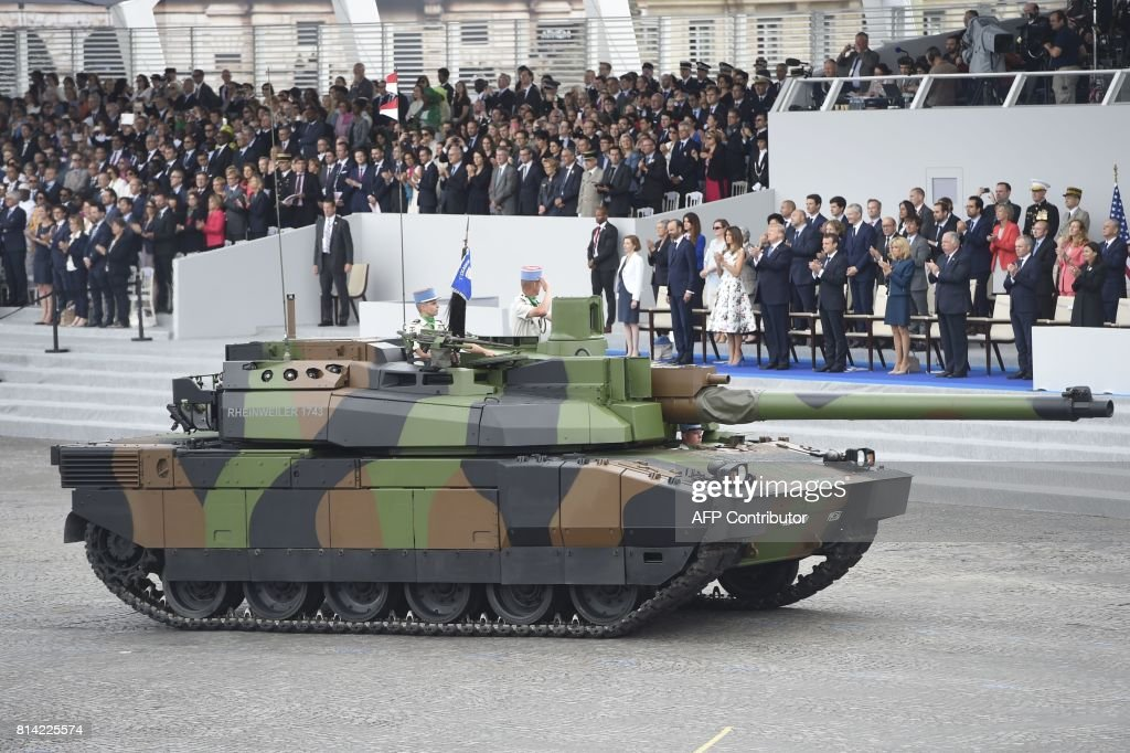 French Defence Minister Florence Parly, French Prime Minister Edouard Philippe, US President Donald Trump and his wife First Lady Melania Trump, French President Emmanuel Macron and his wife Brigitte Macron, Senate President Gerard Larcher, the President of the French National Assembly Francois de Rugy and the Mayor of Paris Anne Hidalgo look at members of the 5e Regiment de Dragons (5th Dragoon Regiment) parading on a Leclerc tank during the annual Bastille Day military parade on the Champs-Elysees avenue in Paris on July 14, 2017. The parade on Paris's Champs-Elysees will commemorate the centenary of the US entering WWI and will feature horses, helicopters, planes and troops. /