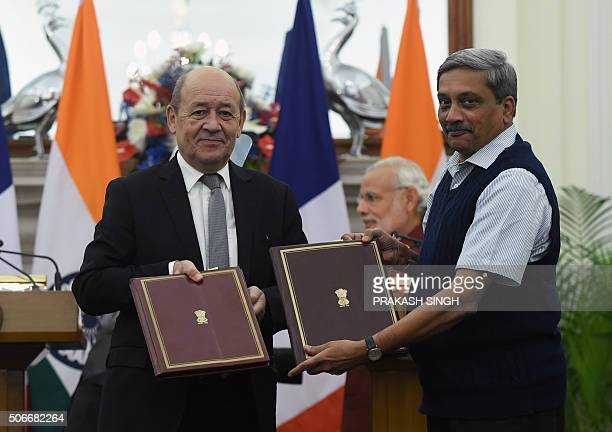 French Defence Minister JeanYves Le Drian and his Indian counterpart Manohar Parrikar show off the intergovernmental agreements for the purchase of...