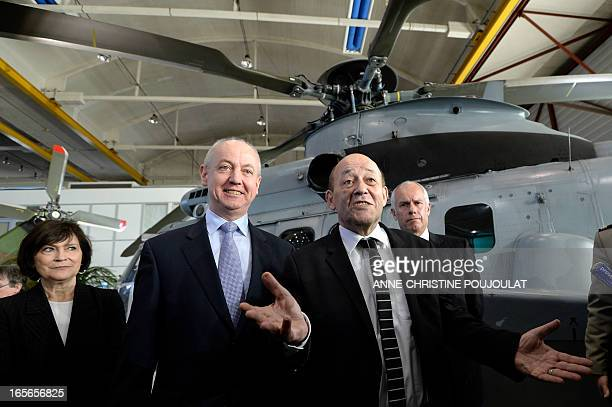 French Defence Minister Jean-Yves Le Drian gestures beside French Junior Minister for Disabled People Marie-Arlette Carlotti and Eurocopter Executive...