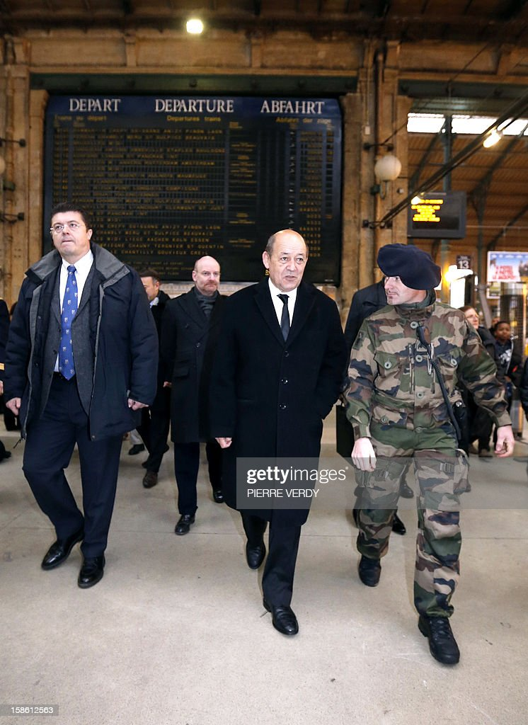 French Defence minister Jean-Yves Le Drian (C) listens to explanations as he visits, on December 21, 2012 at Gare du Nord railway station in Paris, security forces deployed as part of France's national security alert system 'Plan Vigipirate' which is reinforced for the end of the year celebration.