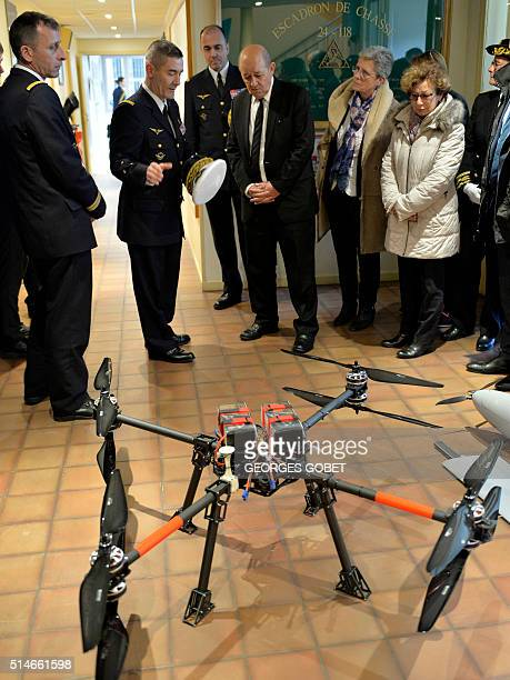 French Defence Minister JeanYves Le Drian listens to the explanations of an officer on the functioning of a drone during his visit to the air base of...
