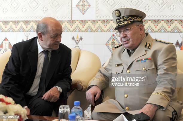 French Defence Minister JeanYves Le Le Drian speaks with Algeria's Chief of Staff General Ahmed Gaid Salah upon his arrival at the HouariBoumediene...
