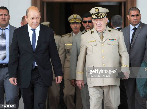 French Defence Minister JeanYves Le Le Drian walks with Algeria's Chief of Staff General Ahmed Gaid Salah upon his arrival at the HouariBoumediene...