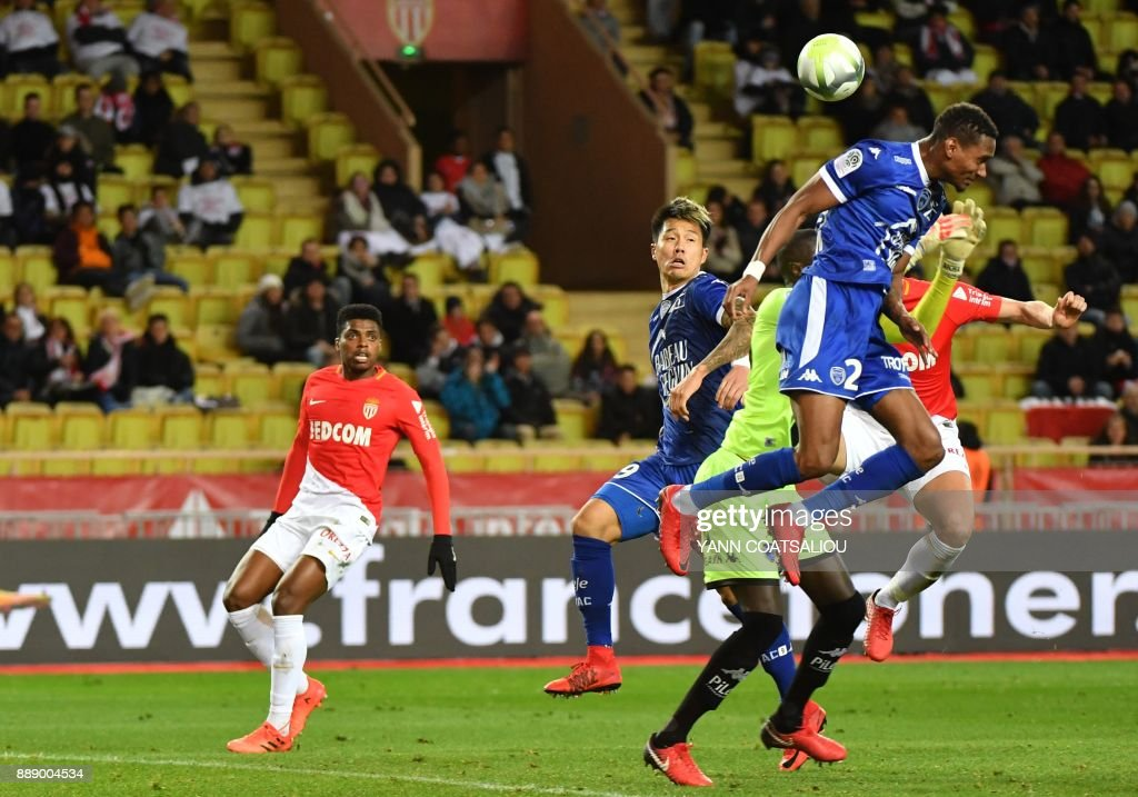 French defender Christophe Herelle (R) leaps in the air to head the ball during the French L1 football match between Monaco (ASM) and Troyes (ESTAC) at The Louis II Stadium in Monaco on December 9, 2017. / AFP PHOTO / Yann COATSALIOU