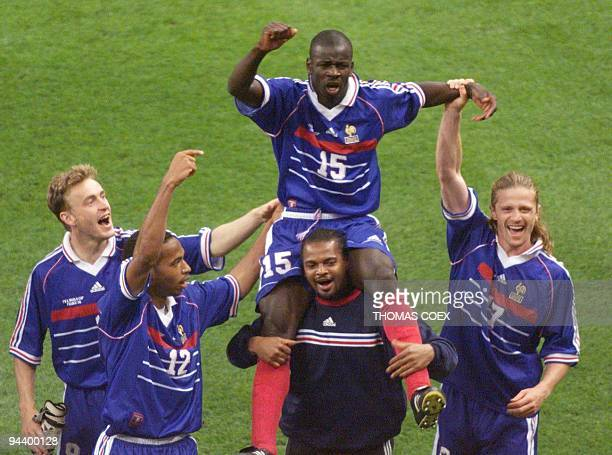 French defender Lilian Thuram who scored the two goals for his team is carried on the shoulders of goalkeeper Bernard Lama as they celebrate with...