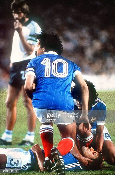French defender Patrick Battiston lies on the ground as midfielder Michel Platini and forward Didier Six surround him while waiting for the medical...