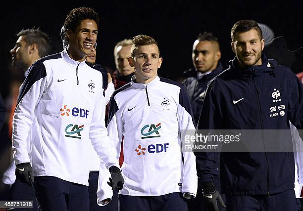 French defender Raphael Varane and French defender Lucas Digne stand next to French forward Andre Pierre Gignac during a training session on November...
