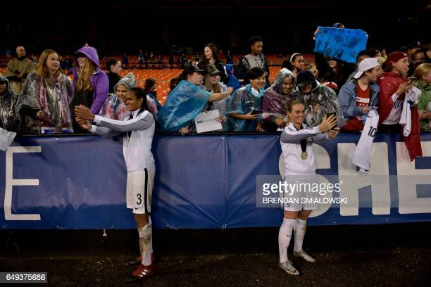 TOPSHOT French defender Wendie Renard and French midfielder Amandine Henry take photos with fans after the She Believes Cup US vs France match at RFK...