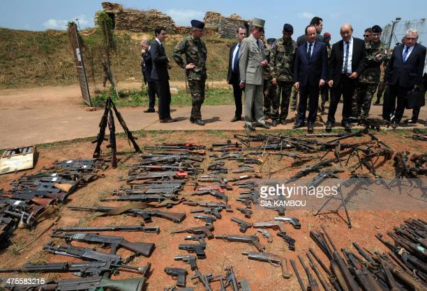 French Defense Minister JeanYves Le Drian and French President Francois Hollande inspect arms confiscated from exSeleka rebels and Antibalaka militia...