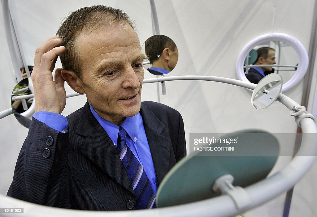 French Denis Thevenin show his invention, a unique system for viewing onces head and hair, set with light and portable mirrors to use for comb, coloring, make-up, shaving, during the opening day of the 36th International Exhibition of Invention, on April 2, 2008 in Geneva. More than 700 exhibitors from 45 countries are present at the World's largest exhibition devoted to innovation in the world.