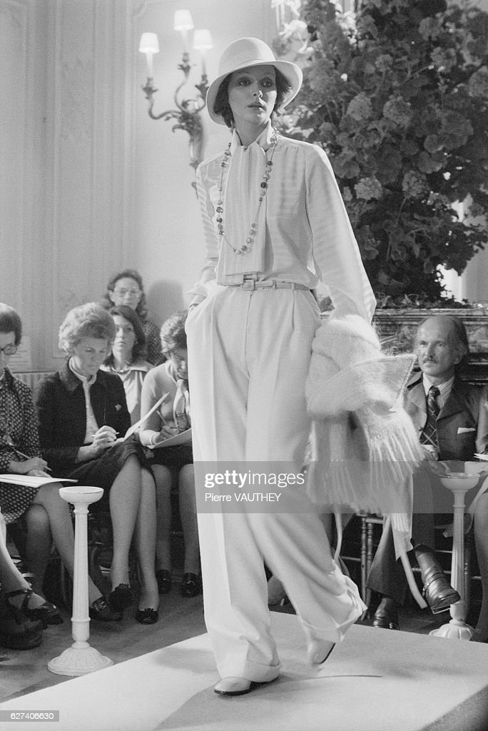French design house Christian Dior shows its 1973-1974 fall-winter women's line in Paris. The model is wearing slacks, a blouse with a long scarf, and a brimmed hat.