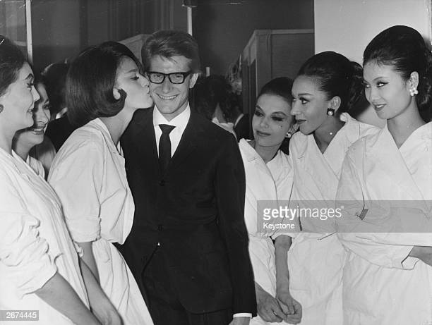 French designer and former Christian Dior employee Yves Saint Laurent receives a kiss from Swedish model Eva Helsing as other models look on, after...