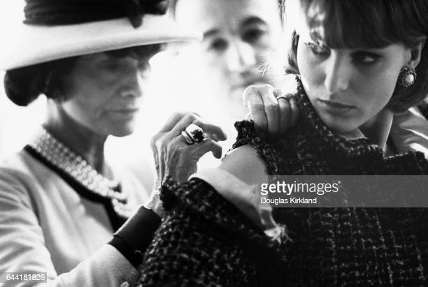 French designer Coco Chanel sews the shoulder of a tweed coat on a fashion model