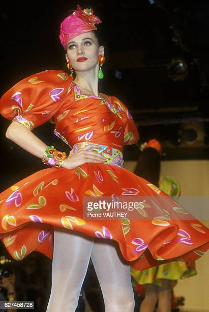 French designer Emanuel Ungaro shows his women's 1991 springsummer haute couture line in Paris The model is wearing a bright orange dress with...