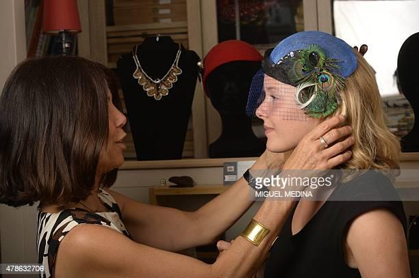 French designer hat and jewelry maker and artist Valerie Drevon adjusts a hat she designed onto a model at her studio in Vincennes outside Paris on...