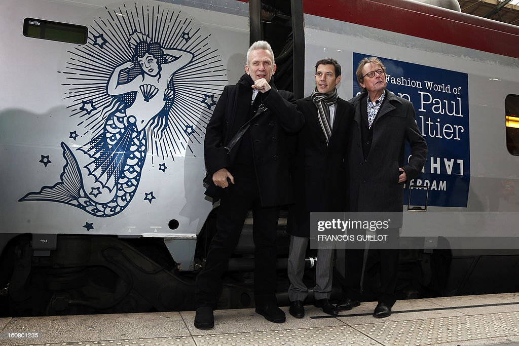 French designer Jean-Paul Gaultier, French CEO of Thalys International, Franck Gervais and a member of the Management Board of Rotterdam Kunsthal museum, Vincent Mentzel, pose on a platform in front of a Thalys train at the Gare du Nord railway station in Paris, on February 6, 2013, as part of the launch of the exhibition 'The Fashion World of Jean Paul Gaultier, from the Sidewalk to the Catwalk', which will run at the Kunsthal museum from February 10 to May 12, 2013 in Rotterdam. On this occasion, Jean-Paul Gaultier signed a drawing and his autograph on a Thalys train painted with blue sailor stripes.