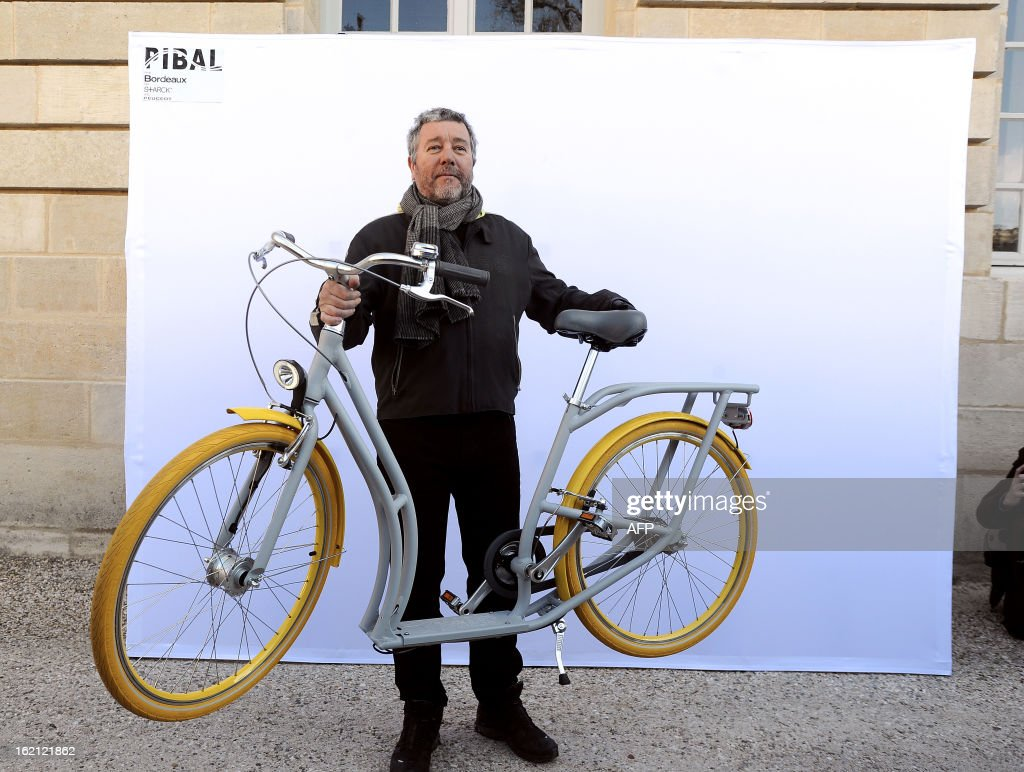 French designer Philippe Starck poses on February 19, 2013 with 'the Pibal', the city of Bordeaux's new hybrid urban bicycle during its presentation at the Town Hall. The bikes, manufactured by Peugeot, should be available in September 2013.