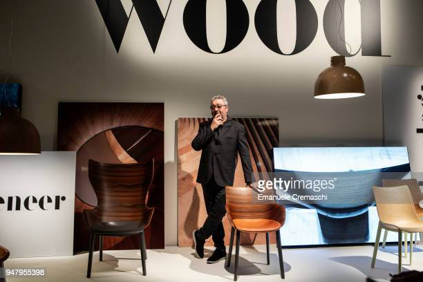 French designer Philippe Starck poses with one of his creations at the Kartell display stand during the Salone Internazionale del Mobile at Fiera di...