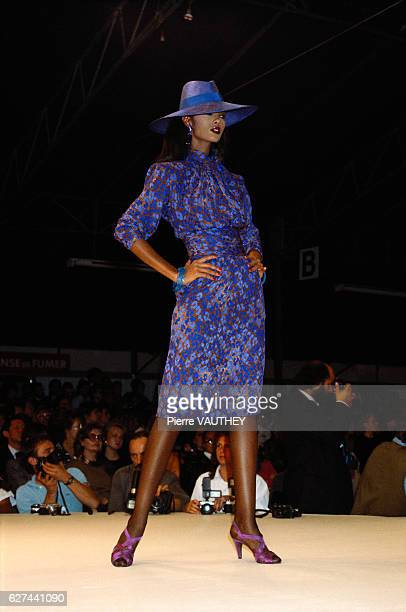 French designer Yves Saint Laurent shows his 1986 springsummer women's readytowear line in Paris Model Iman is wearing a blue floral dress with a...