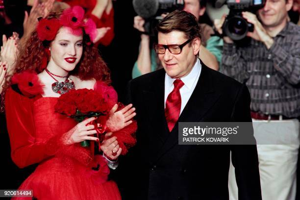 French designer Yves SaintLaurent flanked by a model acknowledges the audience after the presentation of the FallWinter 1994/1995 readytowear...