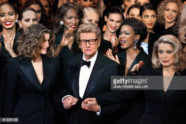 French designer Yves Saint-Laurent salutes the crowd with French model Laetitia Casta and French actress Catherine Deneuve at the Centre Georges...