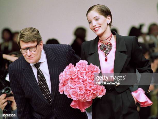 - French designer Yves Saint-Laurent takes to the catwalk next to model wearing a black wool-crepe evening trouserss suit over a pink satin blouse...
