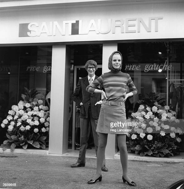 French designer Yves St Laurent standing outside his Rive Gauche boutique in France, with a model wearing a skirt and sweater from his ready-to-wear...