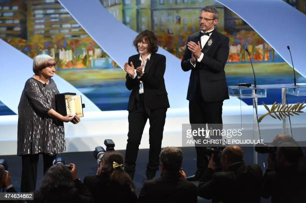 French director Agnes Varda holds her honourary Palme d'Or while posing with British actress and singer Jane Birkin and French actor and Master of...